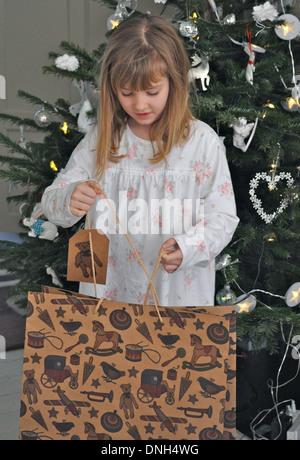 Porträt des Kindes öffnen ein Weihnachtsgeschenk - Stockfoto