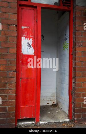 Rote Tür in einem Backstein umgeben in einem weißen Raum führt. - Stockfoto