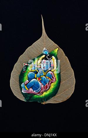 Hand bemalt indischer Krishna Design auf einem heiligen Baum Feigenblatt / Bodhi Baum Blatt auf schwarzem Hintergrund - Stockfoto