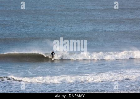 Ein einsamer Surfer auf einer Welle vor der Küste von North Devon am Putsborough. Dieser Küstenabschnitt ist beliebt - Stockfoto