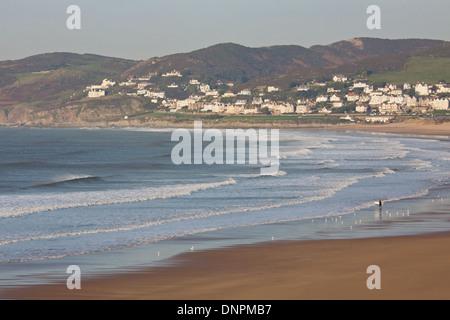 Eine einsame Surfer macht ihren Weg ins Meer auf einen Winternachmittag im Woolacombe Bay in North Devon UK - Stockfoto
