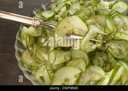 Ein Bild von einen marinierten Gurkensalat in eine Glasschüssel auf Wodd Hintergrund mit einer Silber Gabel. - Stockfoto