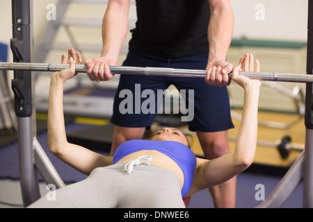 Trainer helfen Frau, heben Sie die Langhantel-Bankdrücken im Fitness-Studio - Stockfoto