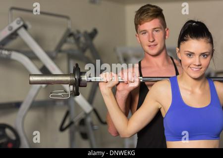 Männlichen Trainer helfen fit Frau, heben Sie die Hantel in Turnhalle - Stockfoto