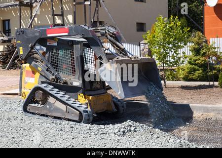 kleine Bagger arbeitet auf Baustelle, bauen neue Straße - Stockfoto