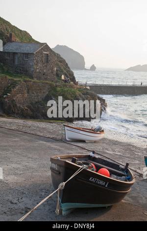 Steinerne Fischerhütte und Boote im Mullion Cove Hafen, Halbinsel Lizard, Cornwall - Stockfoto
