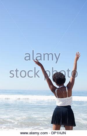 Frau posiert in Wellen am Strand - Stockfoto