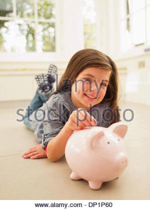 Mädchen, Münze ins Sparschwein - Stockfoto