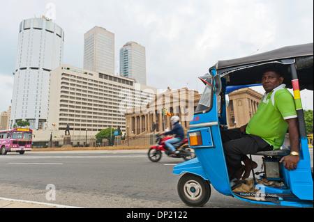 Tuk-Tuk-Fahrer mit dem Gebäude der Bank of Ceylon am Rücken, das alte Parlament, rechts, Colombo, Sri Lanka - Stockfoto