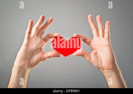 Werden Sie my Valentine, Valentinstag-Konzept. Mann mit rotem Papierherz in den Händen - Stockfoto