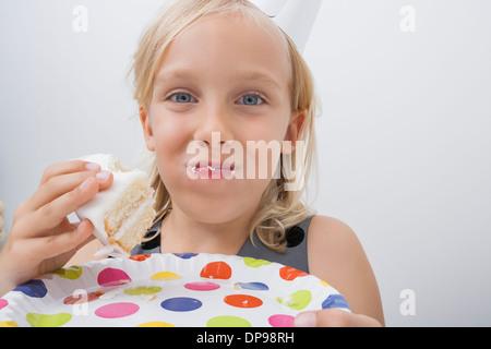Nahaufnahme der niedliche Mädchen essen Geburtstagskuchen vor grauem Hintergrund - Stockfoto