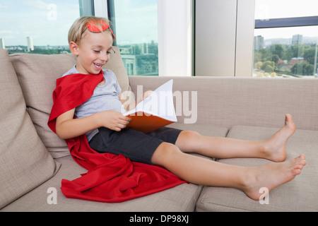 Glückliche kleine Junge in Superhelden-Kostüm Buch zu Hause auf sofa - Stockfoto
