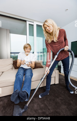 Frau beim Mann spielen Videospiel im Wohnzimmer zu Hause Staubsaugen - Stockfoto