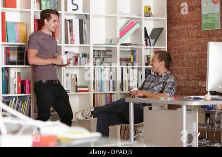Zwei männliche Kollegen chatten im Büro - Stockfoto