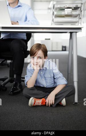 Junge sitzt auf Boden mit Geschäftsmann arbeiten am Schreibtisch - Stockfoto