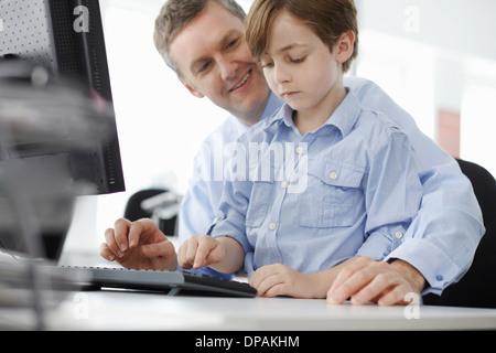 Junge sitzt auf Vaters Schoß mit Computer-Tastatur - Stockfoto