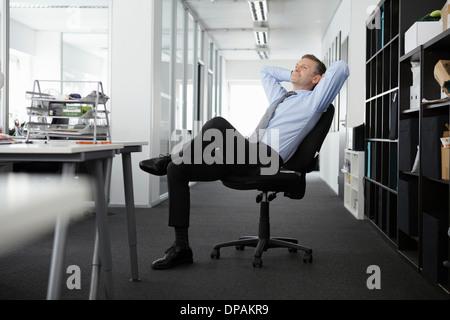 Reife Geschäftsmann in Bürostuhl zurück gelehnt - Stockfoto