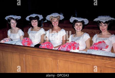 Fünf lächelnde Brautjungfern in passenden weißen Kleidern und Rüschen Hüte erwarten in einer Kirche Bank für eine - Stockfoto