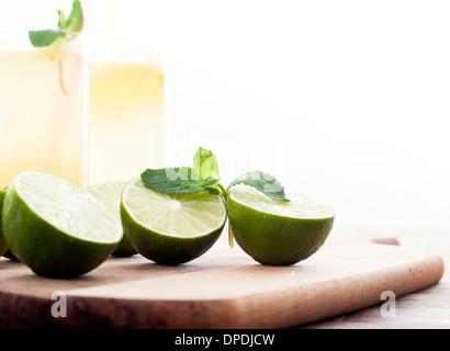 Frische Limetten und Limonade auf hölzernen Hintergrund - Stockfoto
