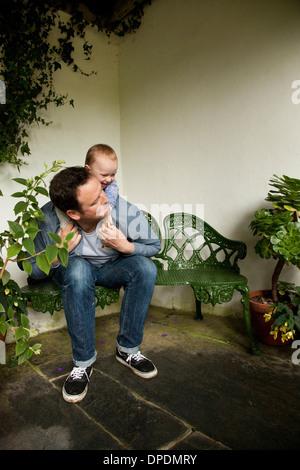Kinder reiten Huckepack auf Vater im Garten - Stockfoto