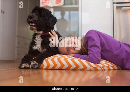 Porträt eines Mädchens auf Kissen liegend mit Hund - Stockfoto