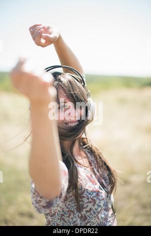 Porträt von Mitte erwachsenen Frau tanzt im Feld mit Arme heben, tragen von Kopfhörern - Stockfoto