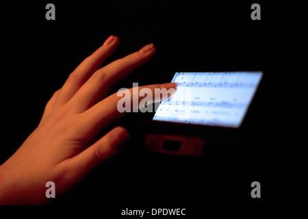 Nahaufnahme von Hand mit Touchscreen Anzeige von Noten Stockfoto