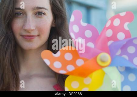 Porträt der jungen Frau, die mit Papier Windmühle - Stockfoto