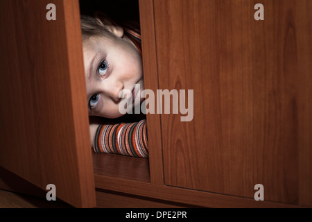 Angst Kind junge versteckt sich im Kleiderschrank - Stockfoto