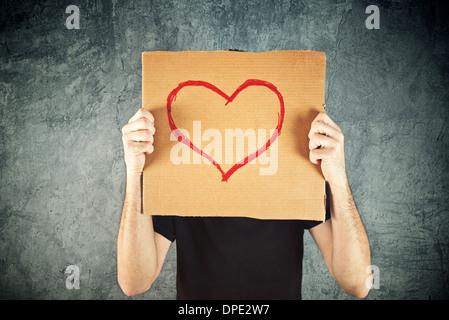 Mann, der Pappe mit Herzform Zeichnung als Valentinstag Konzeptbild hält. - Stockfoto