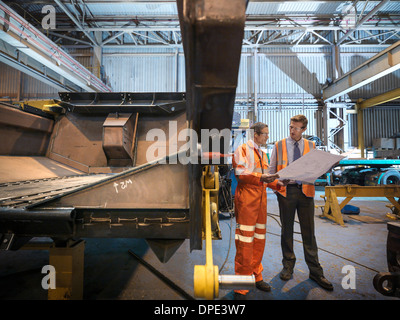 Ingenieure, die Prüfung von Konstruktionszeichnungen in Fabrik - Stockfoto