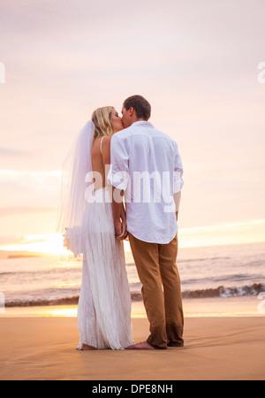 Ehepaar, Braut und Bräutigam küssen bei Sonnenuntergang am wunderschönen tropischen Strand in Hawaii - Stockfoto