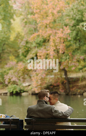 Gay paar umarmt auf Parkbank - Stockfoto