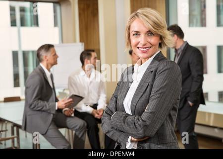 Geschäftsfrau vor Kollegen - Stockfoto