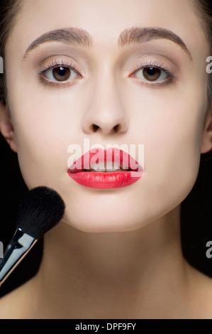Zugeschnittenen Studioaufnahme der ruhige junge Frau und Make up Pinsel - Stockfoto
