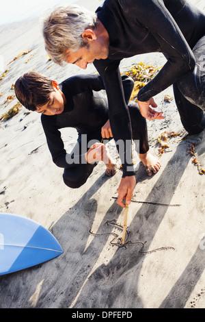Vater und Sohn Surfer am Strand, Encinitas, Kalifornien, USA - Stockfoto