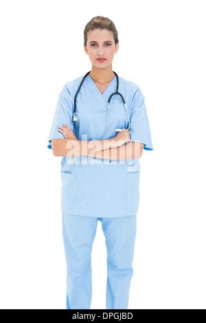 Ernst Braun behaarte Krankenschwester in blau scheuert posiert mit Armen gefaltet - Stockfoto