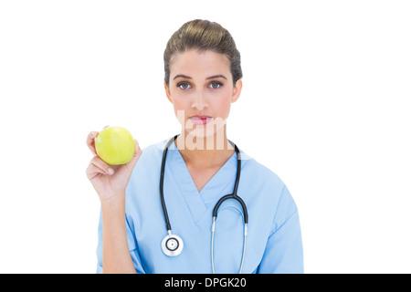 Ernst Braun behaarte Krankenschwester in blau scheuert hält einen grünen Apfel - Stockfoto