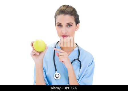 Scrubs – Die Anfänger Heck braunen Haaren Krankenschwester in blau zeigt einen Apfel mit dem finger - Stockfoto