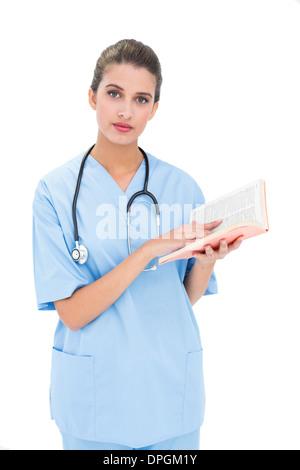 Ernst Braun behaarte Krankenschwester in blau scheuert sich ein Buch hält - Stockfoto