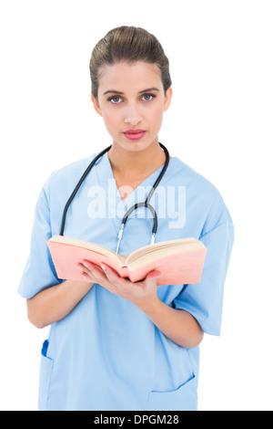 Heck braunen Haaren Krankenschwester in blau scheuert sich ein Buch hält - Stockfoto