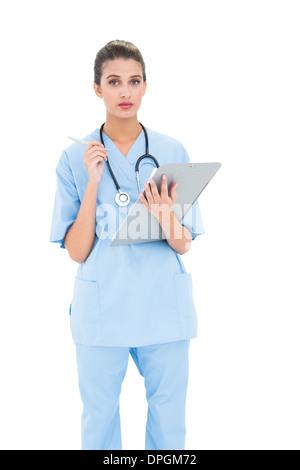 Ernst Braun behaarte Krankenschwester in blau scheuert Bericht prüfen - Stockfoto