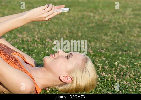 Junge Frau liegt auf dem Rasen mit smartphone - Stockfoto