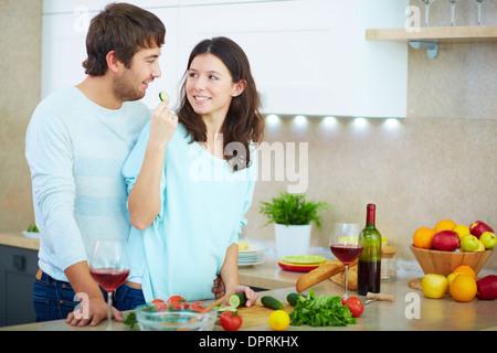 Porträt des jungen Mannes und seiner Frau Gemüsesalat in der Küche kochen - Stockfoto