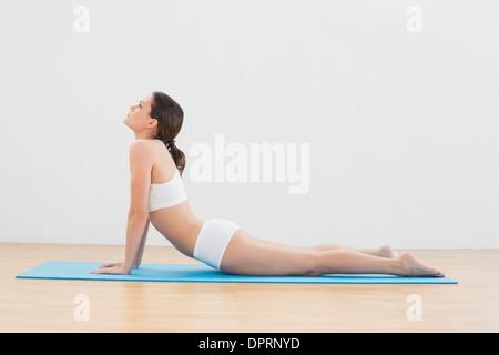Frau macht die Cobra posieren auf Gymnastikmatte - Stockfoto