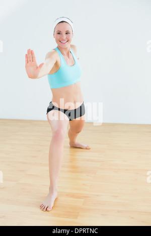 Durchtrainierte Frau tut der Krieger-Yoga pose im Fitness-studio - Stockfoto