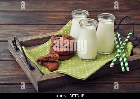 Milch in kleinen Gläsern mit gestreiften Strohhalme und Cookies auf Vintage Tablett - Stockfoto