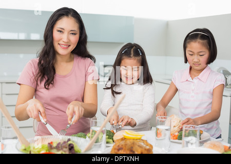 Frau mit zwei kleinen Mädchen, die mit Lebensmitteln in der Küche - Stockfoto