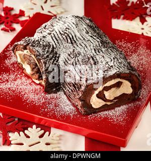 Yule Log Schokolade Schwamm Vanille Creme traditionelle rote Weihnachtsteller Puderzucker bestäuben Snow Flake Dekoration - Stockfoto