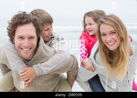Glückliches Paar Huckepack Kinder am Strand - Stockfoto